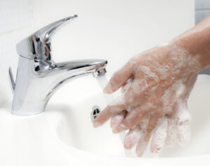 Photo showing a person washing their hands thoroughly with soap under running water